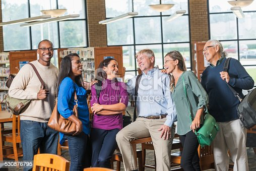 876965270 istock photo Multiracial group of mature students in library 530876795