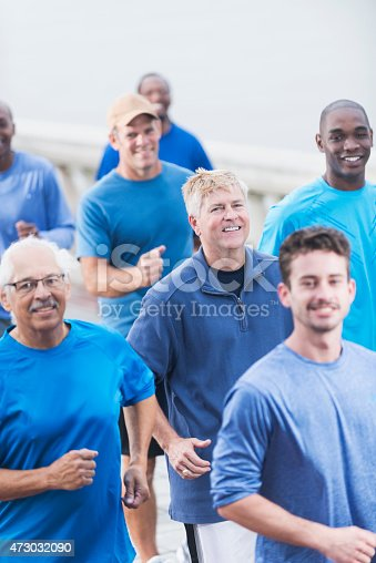 istock Multiracial group of men in blue shirts running 473032090