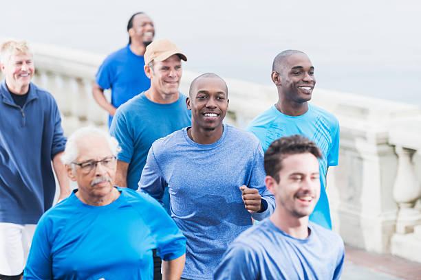 gruppe von personen verschiedener herkunft der männer in blauen hemden running - laufveranstaltungen stock-fotos und bilder