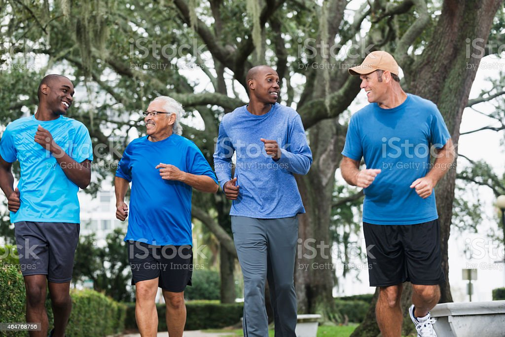 Multiracial group of men running in the park stock photo