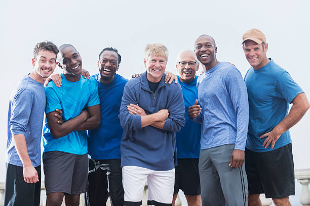 Multiracial group of men wearing blue shirts stock photo