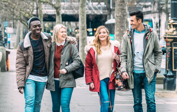 Multiracial group of millenial friends walking at London city center - Next generation friendship concept on multicultural young people on winter fashion cloth having fun together - Soft azure filter stock photo