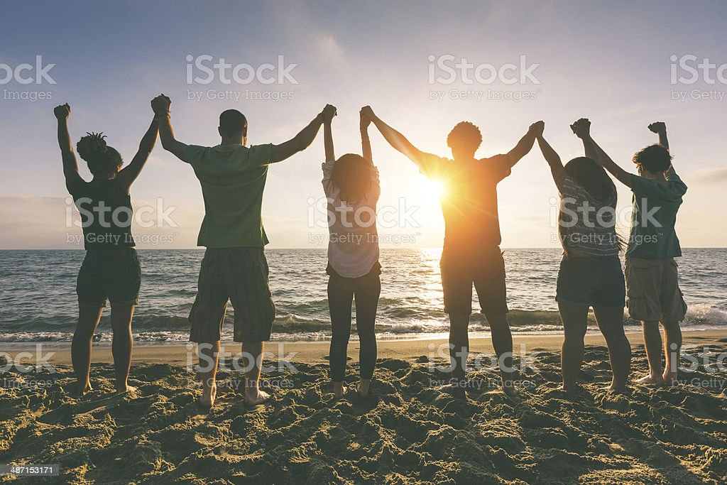 Multiracial Group of People with Raised Arms looking at Sunset royalty-free stock photo