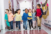istock Multiracial group of preschoolers running down hallway 473895276