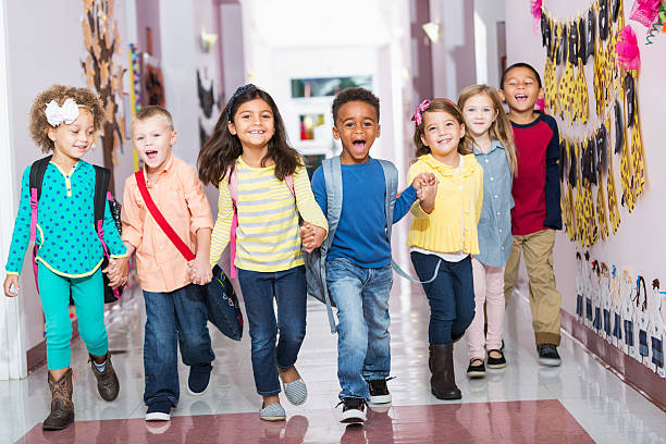 Multiracial group of preschoolers running down hallway A multi-ethnic group of seven children holding hands, running down their school hallway, laughing and shouting, looking at the camera.  The little boys and girls are kindergarten or preschool age, 4 to 6 years. children only stock pictures, royalty-free photos & images