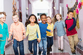 istock Multiracial group of preschoolers running down hallway 483468090