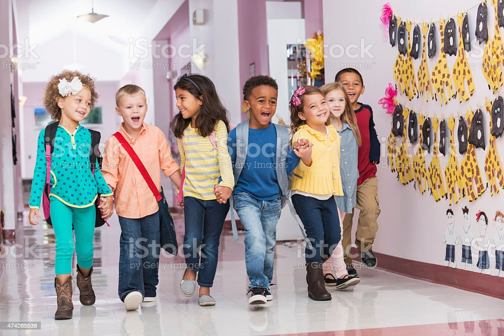 Multiracial group of preschoolers walking down hallway stock photo