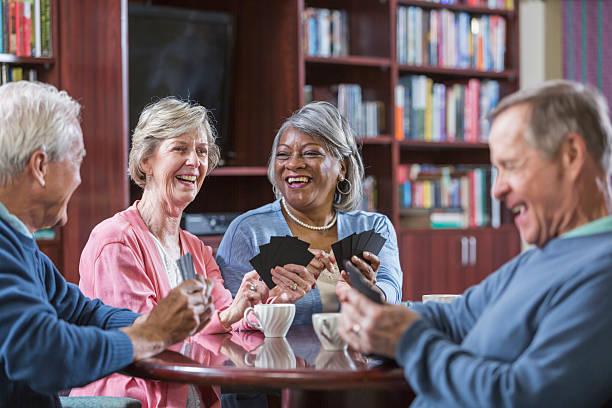 Multirracial Grupo de los mayores hablando, jugar juego de cartas - foto de stock