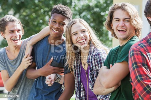 A multi-ethnic group of teenagers hanging out together outdoors. They are in a row, laughing and smiling.