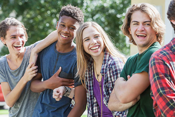 Multiracial group of teenagers handing out outdoors stock photo