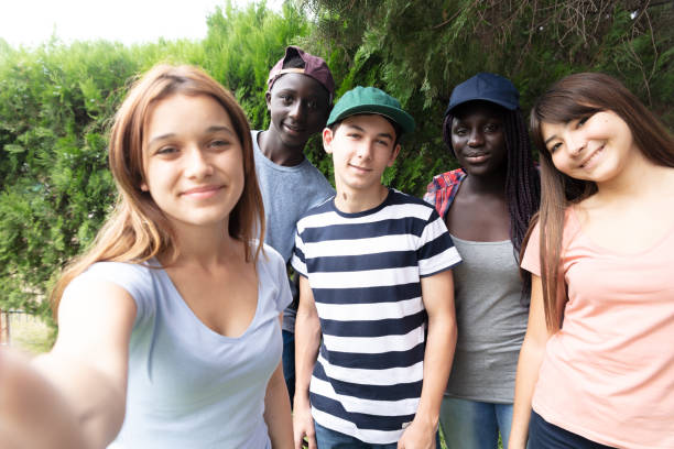 Multiracial group of teenagers in the school park  making a selfie Multiracial group of teenagers in the school park  making a selfie. teenagers only stock pictures, royalty-free photos & images