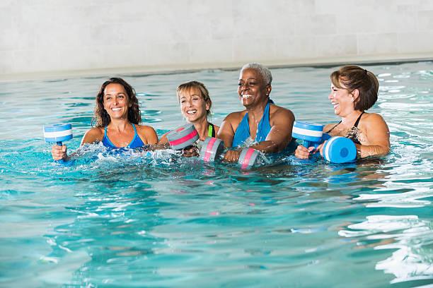 Multiracial group of women in water aerobics class stock photo