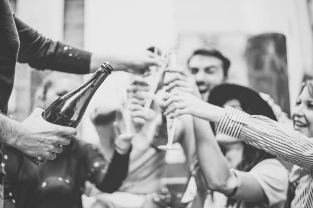 gemischtrassigen gruppe junger freunde spaß trinken und toasten gläser champagner auf universität treppe - glückliche menschen feiern abschluss mit einer flasche prosecco in der stadt im freien - schaumwein fotos stock-fotos und bilder