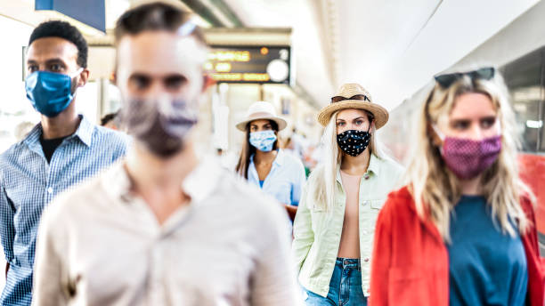 Multiracial group walking with serious face expression at railway station - New normal travel concept with young people covered by protective mask - Focus on blond girl with hat stock photo