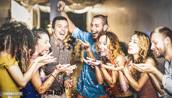 istock Multiracial happy friend having fun at new year's eve celebration - Young people blowing confetti at after party in night club - Friendship concept on cool entertainment mood - Focus on blue shirt guy 1069841076