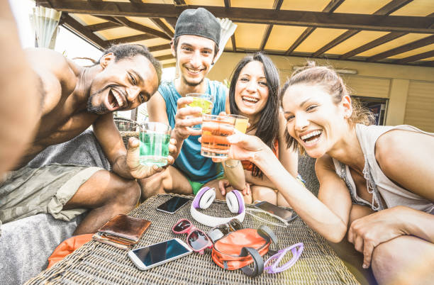 Multiracial happy friends group taking selfie and having drunk fun with cocktail at beach resort - Summer concept and multi ethnic friendship at bar restaurant - Sunny afternoon filtered color tones stock photo