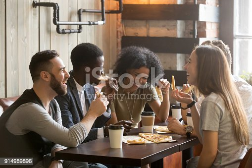 istock Multiracial happy young people laughing eating pizza together in pizzeria 914989896