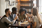 Multiracial happy young people laughing eating pizza together in pizzeria