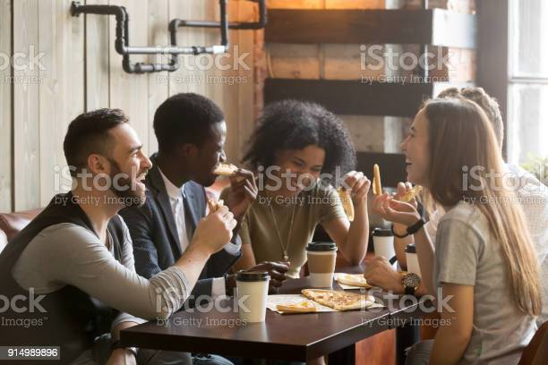 Multiracial happy young people laughing eating pizza together in picture id914989896?b=1&k=6&m=914989896&s=612x612&h=e 2tpbigzqa5vay2f6gaexeui8 lv vizxmn8vu80rk=