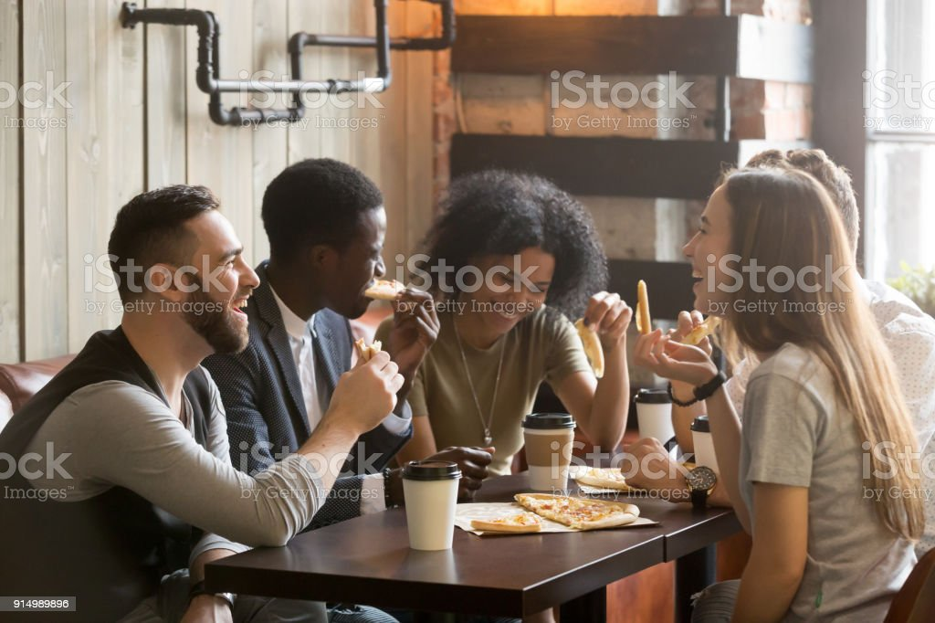 Multiracial happy young people laughing eating pizza together in pizzeria stock photo