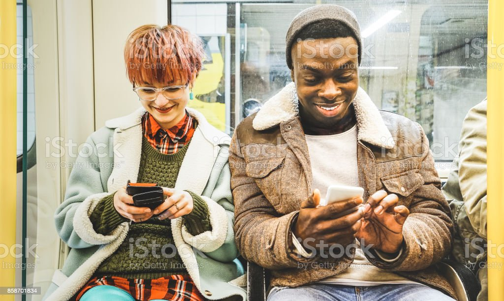 Multiracial hipster friends couple having fun with smartphone in subway train - Urban relationship concept with young people watching mobile phone in city underground area - Bright desaturated filter stock photo
