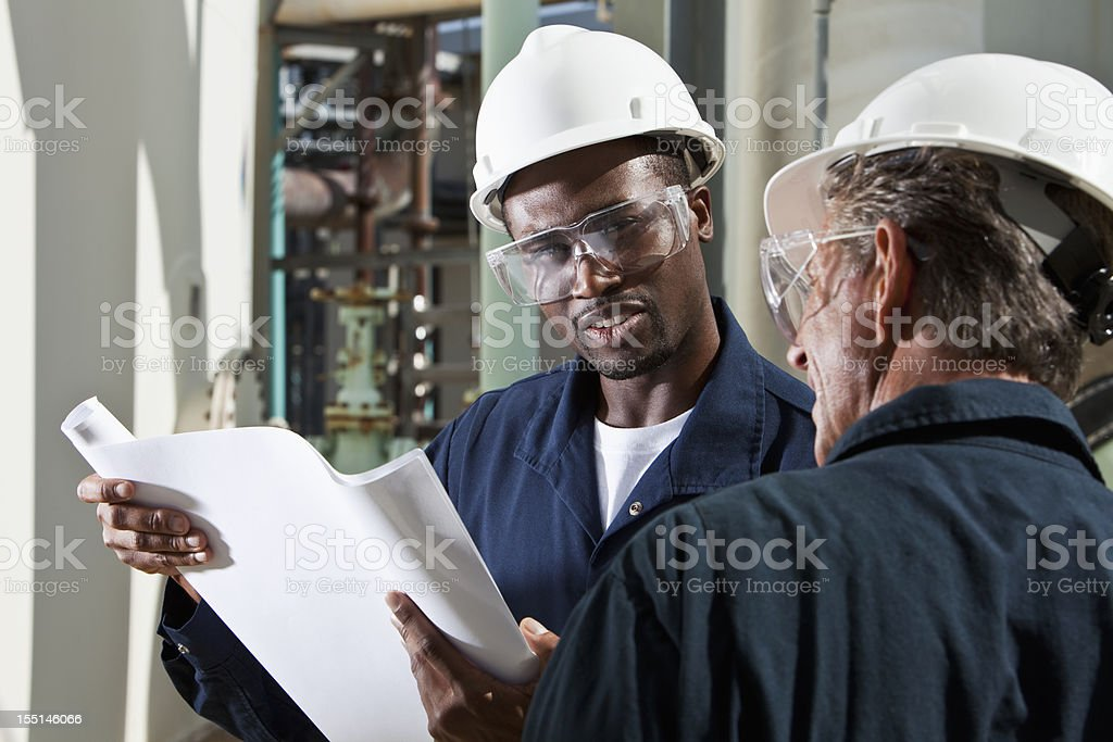 Multiracial industrial workers reviewing plans stock photo