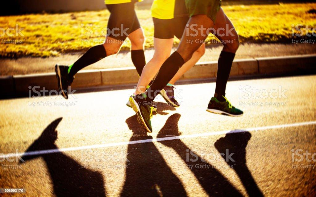 Multiracial joggers run on the road stock photo