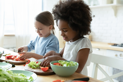 African and Caucasian little girls best friends cooking together in modern kitchen. Multiracial cousins hold knives cutting vegetables on wooden board prepare healthy salad making surprise for parents