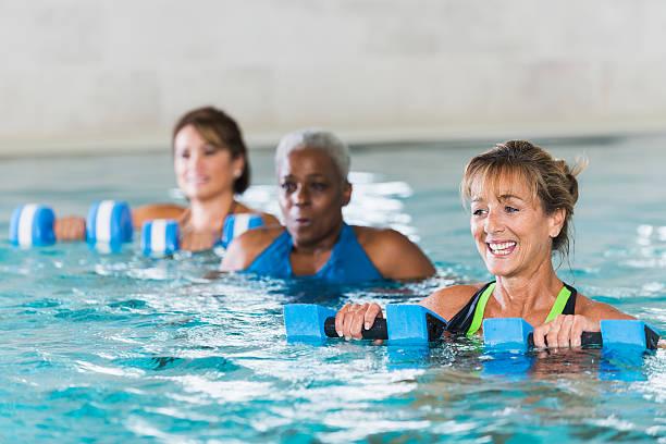 Multirazziale mature donne in classe di aerobica in acqua - foto stock