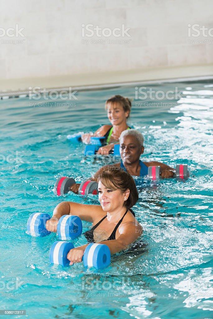 Multiracial mature women in water aerobics class stock photo