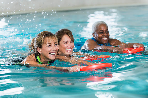 Multiracial middle-aged women swimming in pool stock photo
