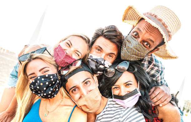 Multiracial milenial friends taking selfie smiling behind face masks - New normal summer friendship concept with young people having fun together - Warm bright backlight filter with tilted composition stock photo
