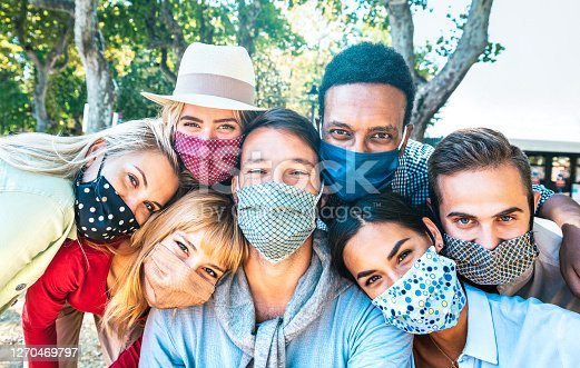 istock Multiracial milenial friends taking selfie with closed face masks during Covid second wave outbreak - New normal lifestyle concept with young people having fun together - Bright vivid backlight filter 1270469797