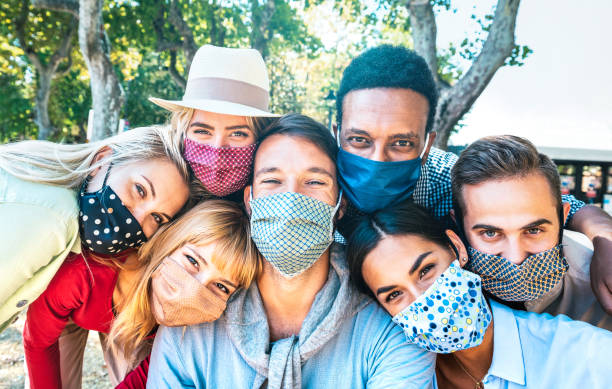 Multiracial milenial friends taking selfie with closed face masks during Covid second wave outbreak - New normal lifestyle concept with young people having fun together - Bright vivid backlight filter stock photo