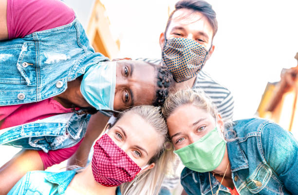 Multiracial millenial friends taking selfie smiling behind face masks - Happy friendship and new normal concept with young people having fun together - Bright sunshine filter with focus on left girl stock photo