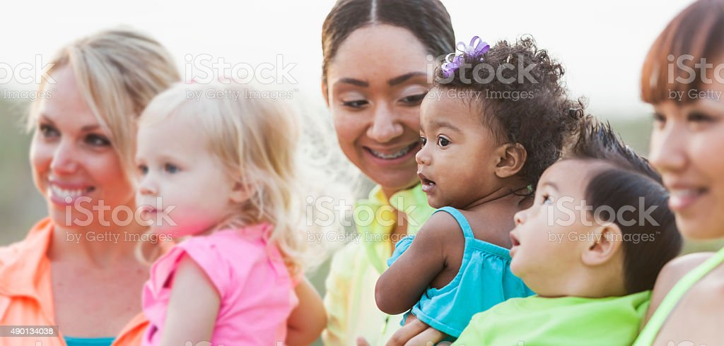 Multi-racial moms and babies, focus on black baby girl stock photo