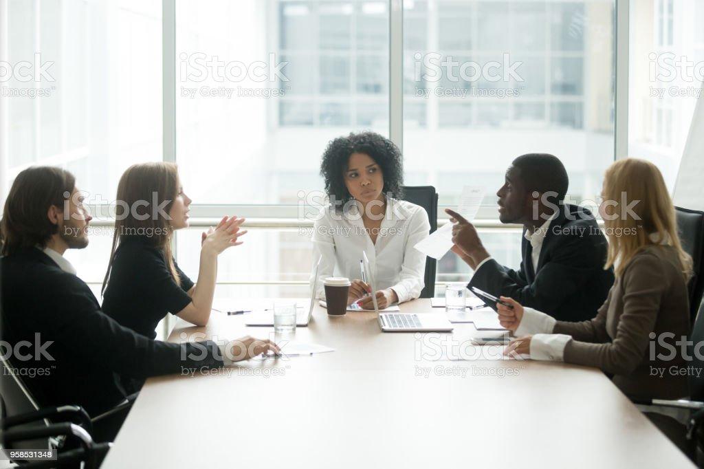 Groupe de personnes multiraciales ayant le différend au sujet du contrat mauvais lors de réunion - Photo
