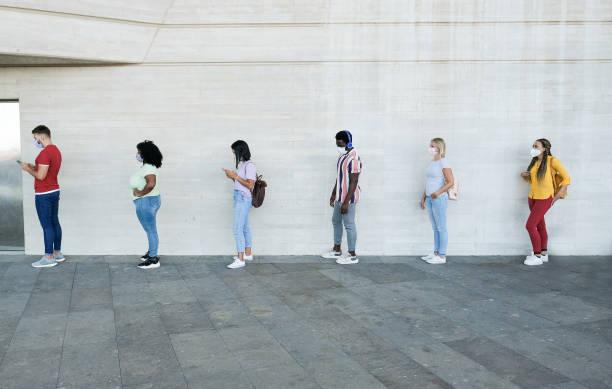 những người đa chủng tộc đứng xếp hàng và chờ đợi - những người trẻ tuổi có cách ly giao tiếp xã hội và đeo khẩu trang bảo vệ - khái niệm về tính bình thường mới và cách ly giao tiếp xã hội - waiting hình ảnh sẵn có, bức ảnh & hình ảnh trả phí bản quyền một lần