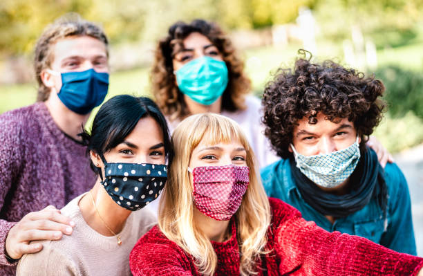 Multiracial people taking selfie wearing face mask and spring clothes - New normal lifestyle concept with young friends having fun together outside - Bright filter with focus on central blond girl stock photo