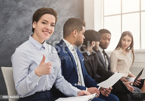 Cheerful woman showing thumb up, multiethnic people waiting in queue. preparing for job interview and reading cv, copy space