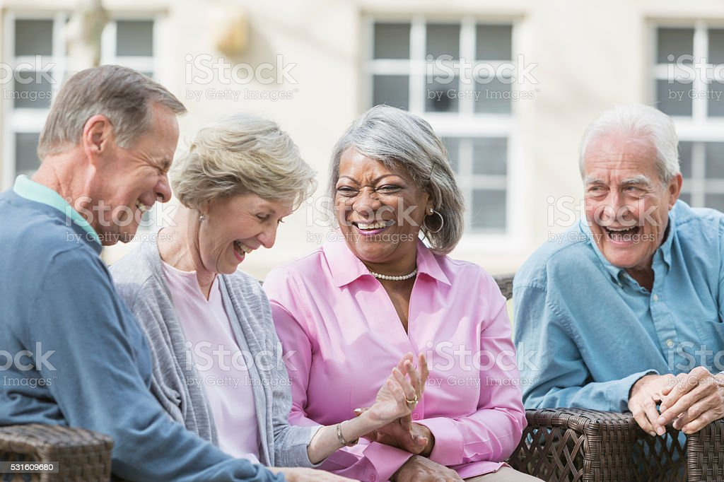 Multiracial senior friends sitting outdoors on patio talking stock photo