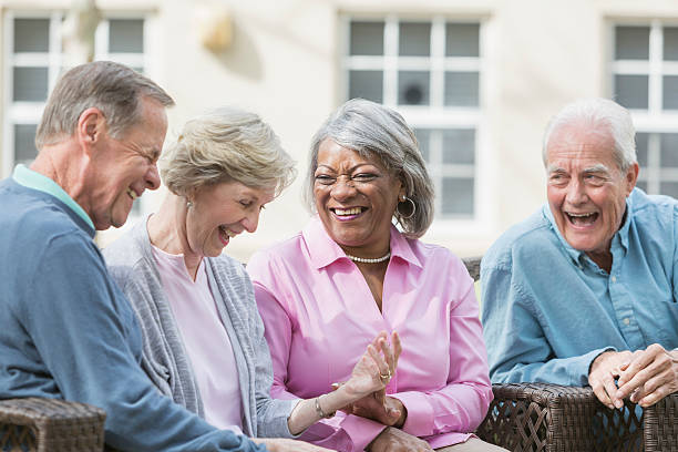 multiracial senior friends sitting outdoors on patio talking - elderly group stock photos and pictures