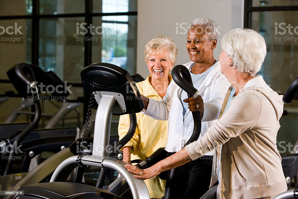 Multiracial senior women in fitness center on elliptical trainer royalty-free stock photo