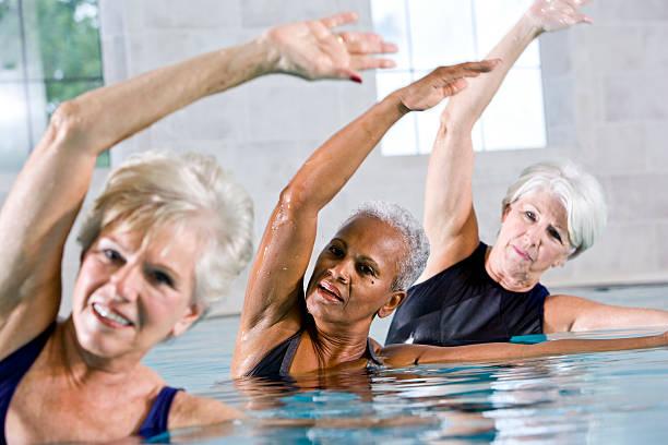 Multirazziale senior donne in classe di Aerobica acquatica - foto stock