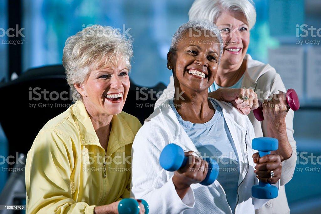 Multirazziale senior donna sollevamento pesi a mano - foto stock