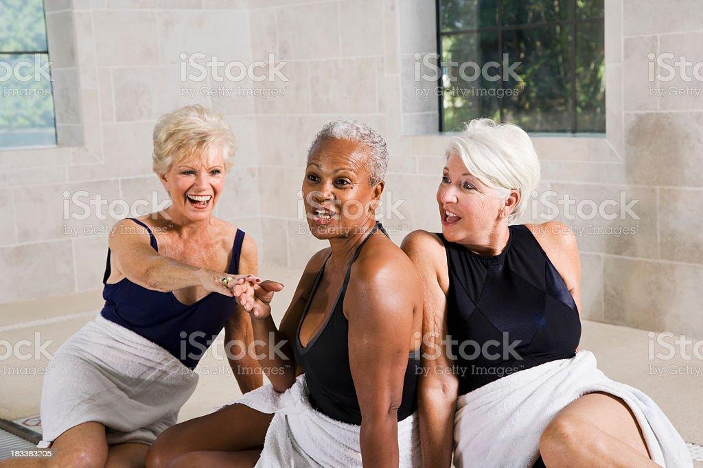Multiracial senior women sitting poolside royalty-free stock photo