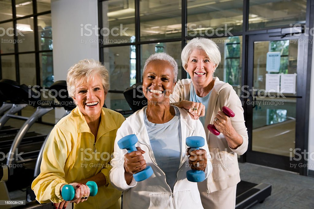 Multiracial senior women staying fit in the gym lifting handweig stock photo