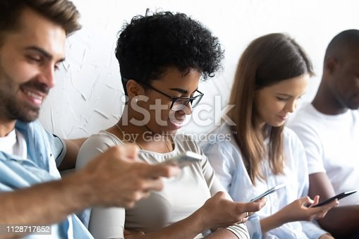 istock Multiracial students sitting together with mobile phones 1128717652
