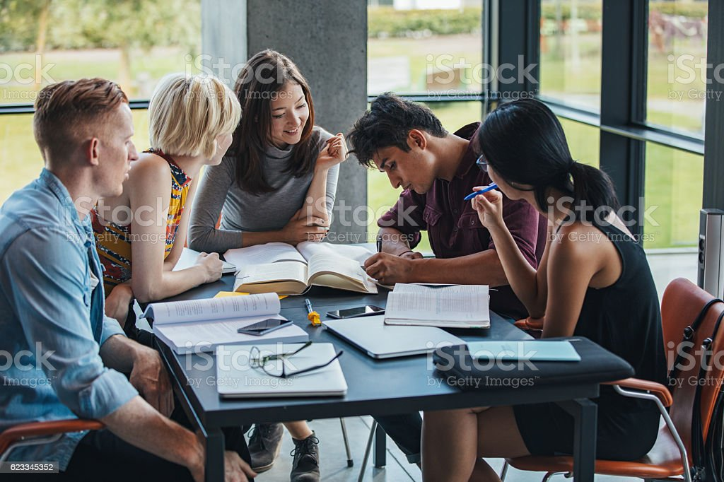 Multiracial students studying together in a library stock photo