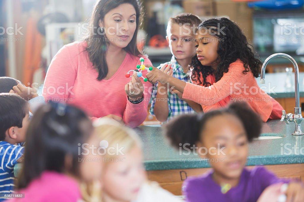 Multiracial teacher and children in science lab - foto de acervo